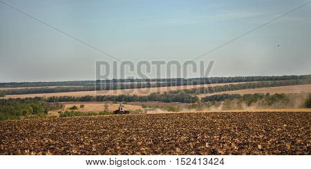 Wheeled tractor plows arable land in dust