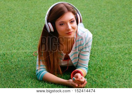 Girl lying on the grass and listening to music