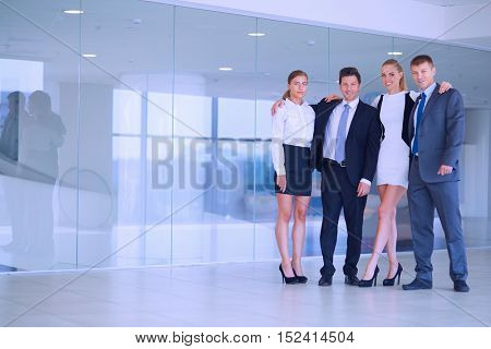 Young businesspeople standing in modern office lobby.