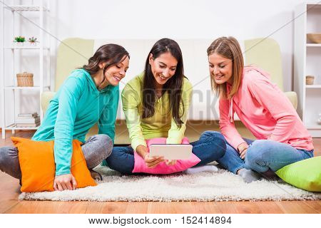 Three friends are sitting in room and using digital tablet.