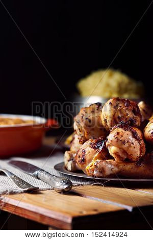 Close view of grilled chicken legs, knife, and fork mash potatoes on a table on a black background. Dark photo. Vertical shot