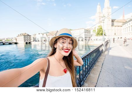 Young female tourist making selfie photo with cityscape view on the river and old town in Zurich city. Having happy vacations in Switzerland