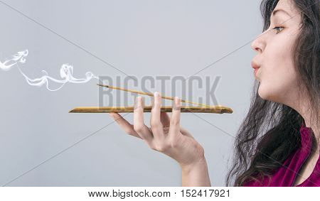 Woman's portrait with incense stick in her hand