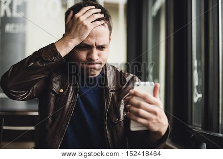 Closeup portrait, stressed young man in purple sweater, shocked surprised, horrified disturbed, by what he sees on his cell phone, isolated indoors background