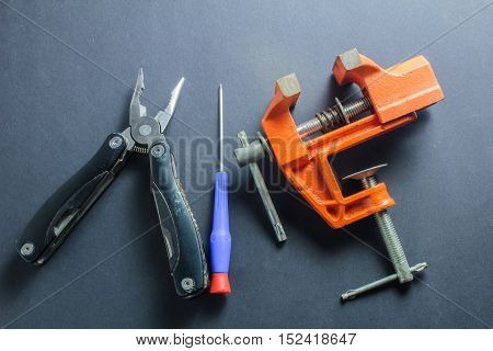 Pliers, Screwdriver And Vise On The Dark Background