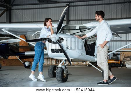 Full length of happy young couple standing near small plane