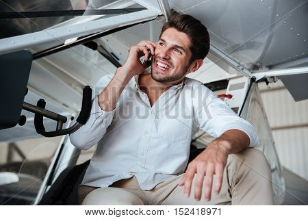Cheerful young man sitting in plane and talking on mobile phone