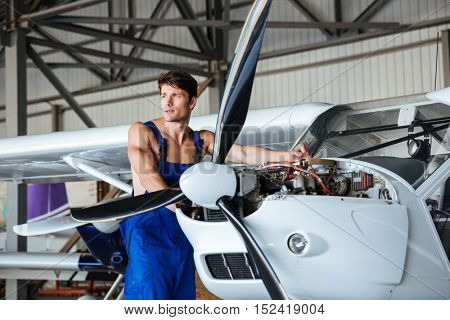 Handsome young repair man fixing plane engine at angar
