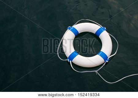 Lifebuoy lifebelt on sea surface as safe help hope protection security concept background
