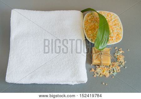 Handmade soap, a white towel, sea salt for body care.