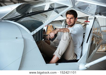 Portrait of attractive young man pilot in small aircraft