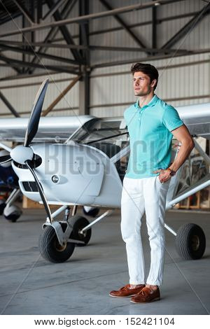 Full length of serious attractive young man standing in front of small aircraft