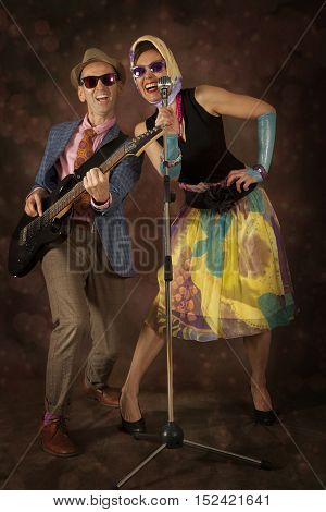 Rockabilly couple having fun playing the guitar and singing on a colorful background