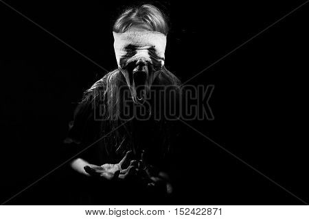 scared bloody girl screaming on black background with copyspace, monochrome