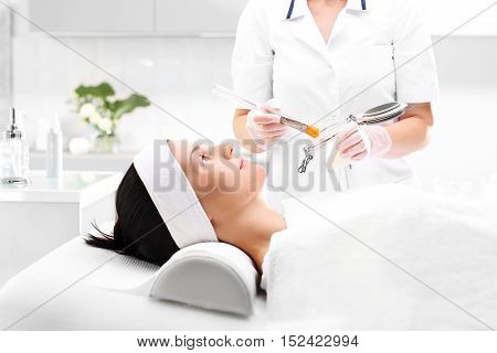 Applying the mask in beauty salon Brush application face masks
