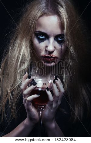 blond witch with bloody glass on black background, toned image