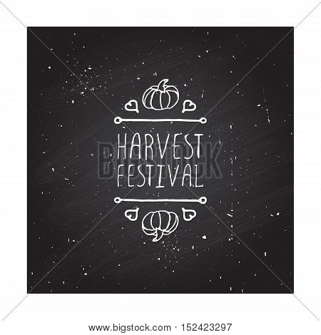Hand-sketched typographic element with pumpkin, maple leaves and text on blackboard background. Harvest festival