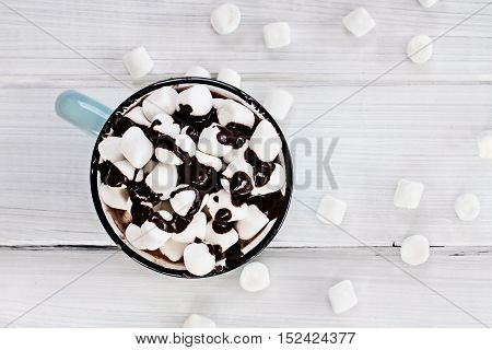 Overhead view of a cup of hot chocolate with marshmallows drizzled with chocolate sauce.