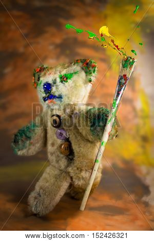 Multicolor paintbrush in hand of a magician teddy bear covered in paint