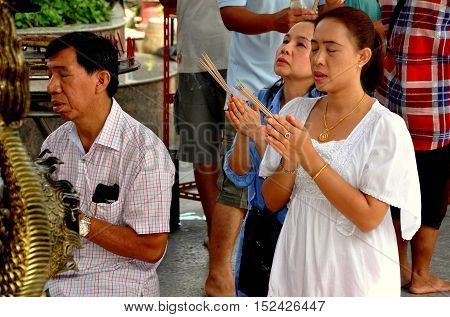 Phuket City Thailand - January 8 2012: Devout Thai-Chinese people holding incense sticks as they pray with clasped hands at the Guan Yin Chinese temple