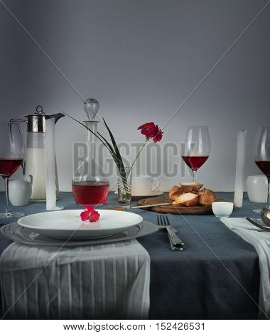 jug of milk, rose wine in glasses, bun, white candles on a blue tablecloth