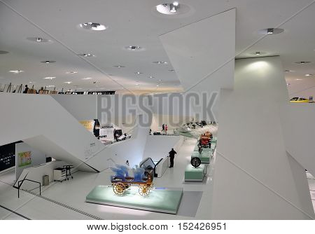 STUTTGART, GERMANY - APRIL 21, 2015. The white interior of the Porsche cars museum. The two-story white space. Huge support in the interior. The exposition of the carriage. Stuttgart, Germany.