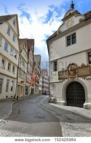 Tubingen, Germany - April 17, 2016: Old narrow street of Tubingen with stone paving half-timbered houses and arched gates.