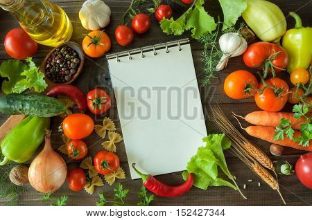 Fresh harvest from the Garden of vegetables and nuts on a wooden background with Notepad