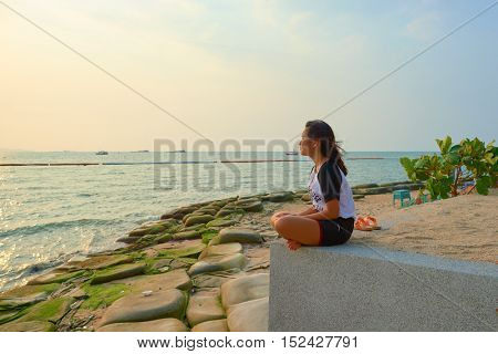 PATTAYA, THAILAND - 20 FEBRUARY, 2016: woman sitting alone and looking to sea in Pattaya. Pattaya is a resort city in Thailand. It is on the east coast of the Gulf of Thailand