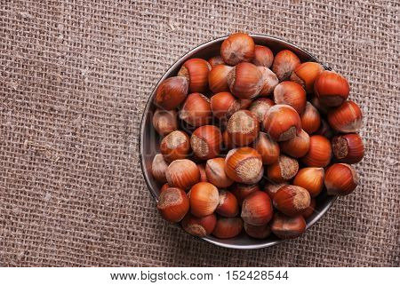 Metal Cup with hazelnut on a fabric background