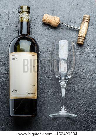 Wine bottle and corkscrew on the graphite board. Wine glass.