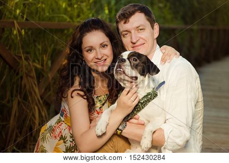 Man and woman sitting with dog looking at the camera