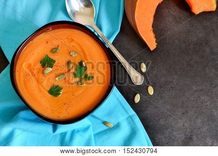 Warm soup puree of pumpkin carrot and celery on a black background
