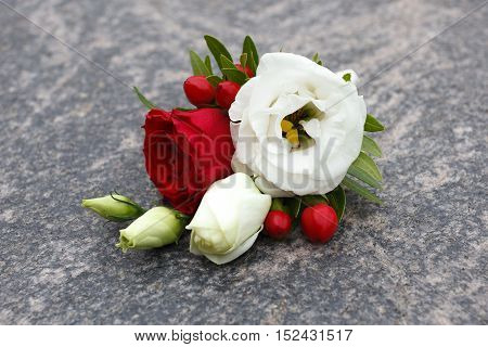 White and red boutonniere isolated on grey background