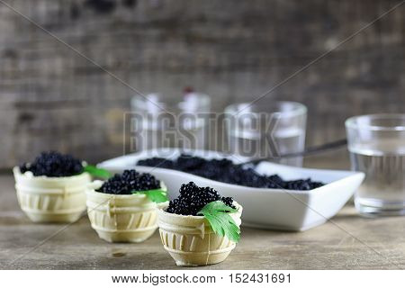 black caviar in the portion on a wooden background