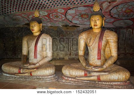 DAMBULLA, SRI LANKA-JUL 24, 2015: Two ancient sculptures of the seated Buddha in cave Buddhist temple (approximately I century BC). Religious landmark  of the city Dambulla