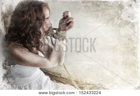 Portrait of a young red-haired girl on a background of gray plaster wall