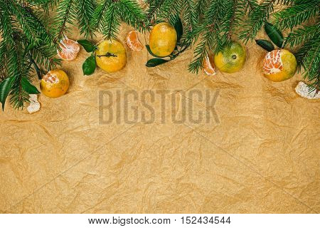 Top framework of mandarins with  evergreen twigs over wrinkled peach colored tissue paper surface