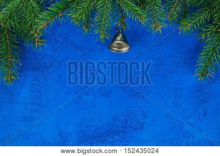 Top framework of evergreen twigs with metal bell over painted blue surface