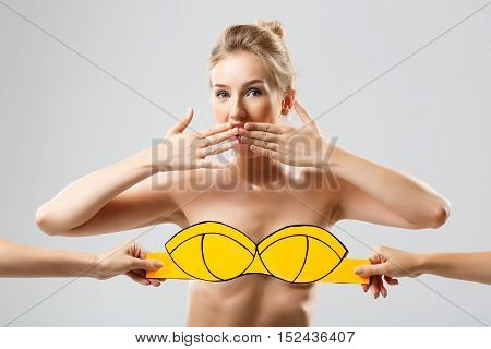 Hands covering beautiful blonde girl with yellow swimwear over white background. Copy space.