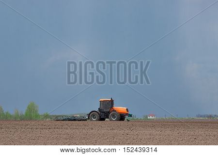 Tillage - tractor preparing the soil for seeding with a cultivator under the rain