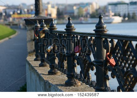 several padlocks on the fence along the city waterfront