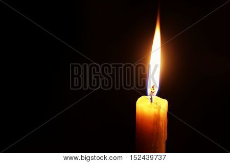 the flame of a burning candle on a black background isolated religion