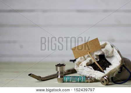 drug addiction concept bong for smoking marijuana and a bag on a wooden background