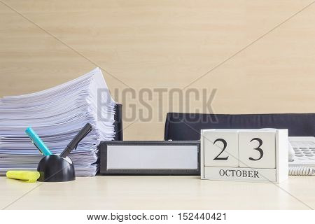 Closeup white wooden calendar with black 23 october word on blurred brown wood desk and wood wall textured background in office room view with copy space selective focus at the calendar