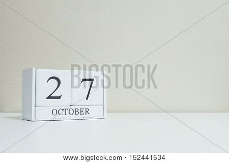 Closeup white wooden calendar with black 27 october word on blurred white wood desk and cream color wallpaper in room textured background with copy space selective focus at the calendar