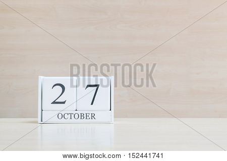 Closeup surface white wooden calendar with black 27 october word on blurred brown wood desk and wood wall textured background with copy space selective focus at the calendar