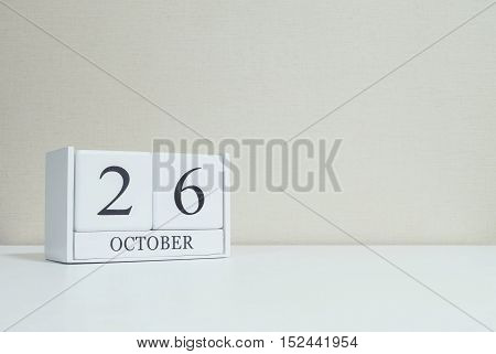 Closeup white wooden calendar with black 26 october word on blurred white wood desk and cream color wallpaper in room textured background with copy space selective focus at the calendar