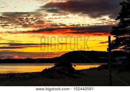 dramatic red unset at norwegian fjord in autumn