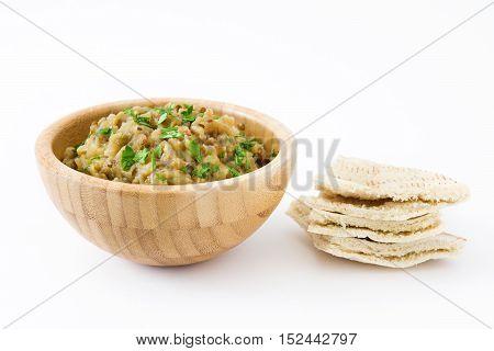 Eggplant baba ganoush and pita bread isolated on white background